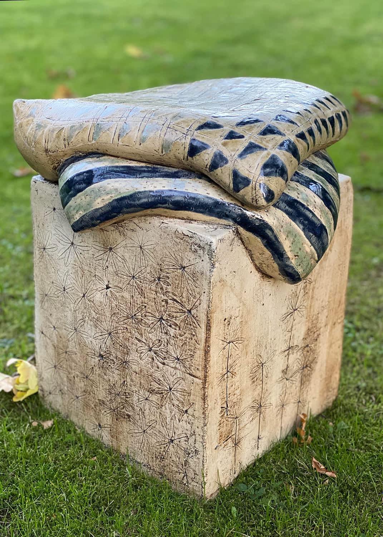 Keramisk skulptur med 2 puder på en græsplæne