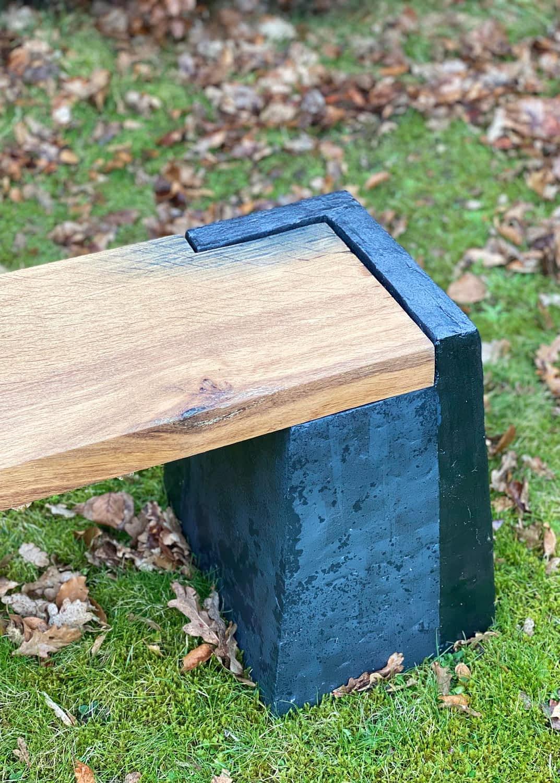 Træplanke på sort bænkestolpe på en græsplæne