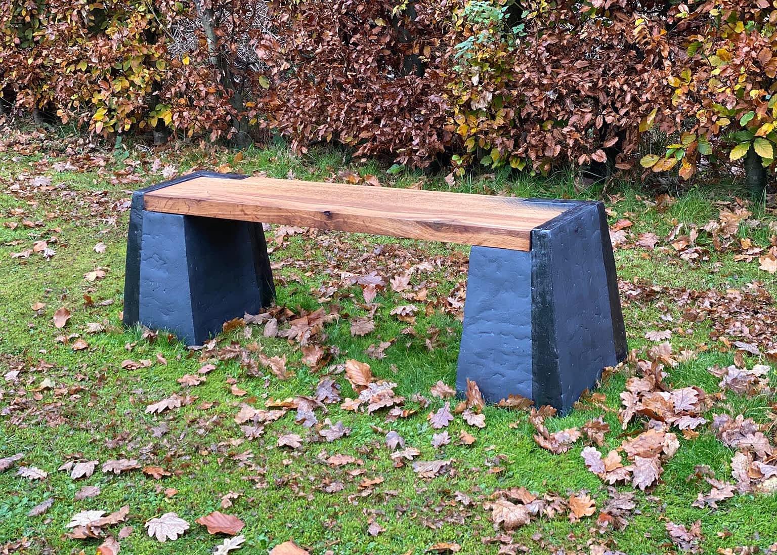 Keramisk sort bænk med træplanke på græsplæne