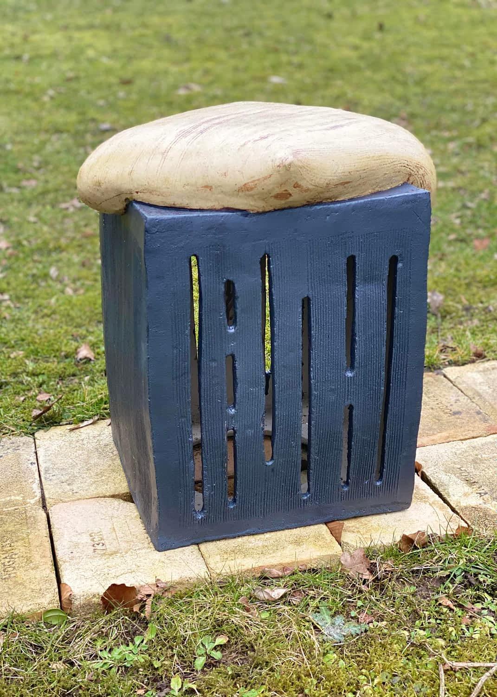 Lys pude på sort kasse med huller på en græsplæne