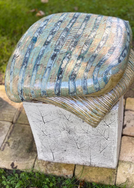Keramisk skulptur med 2 puder på en græsplæne med fliser
