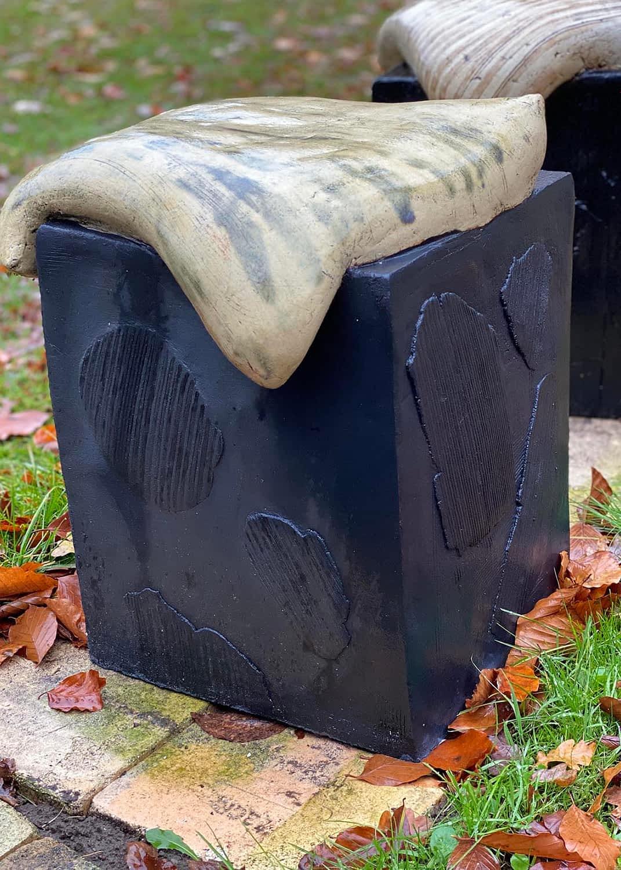 Lys pude på sort kasse på en græsplæne