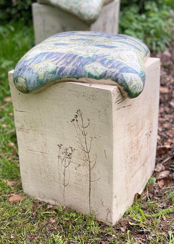 Siddeskammel med pude på en græsplæne